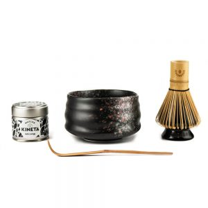 30g Tin Of Kineta Matcha Tea, Black Tea-Masters Chawan Matcha Bowl with A Purple Bamboo Chashuku Bamboo Spoon In Front Of It, And A Chasen Matcha Whisk On A Ceramic Holder