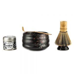 30g Tin Of Kineta Matcha Tea, Black Tea-Masters Chawan Matcha Bowl With A Purple Bamboo Chashuku Bamboo Spoon Resting On It, And A Chasen Matcha Whisk On A Ceramic Holder