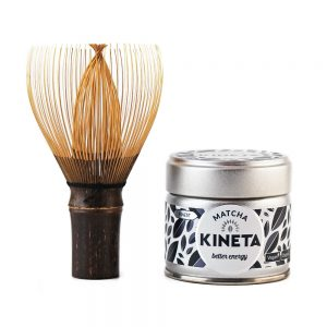 Hand-Crafted Japanese Bamboo Chasen Matcha Whisk Stood On Its Handle Next To A 30g Tin Of Kineta Finest Matcha Tea