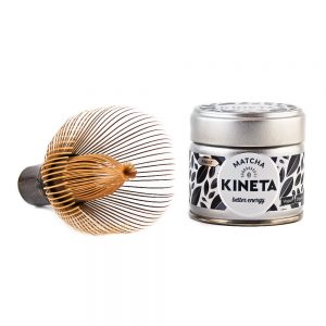 Hand-Crafted Japanese Bamboo Chasen Matcha Whisk Resting With Its Tines Facing Forward Next To A 30g Tin Of Kineta Finest Matcha Tea