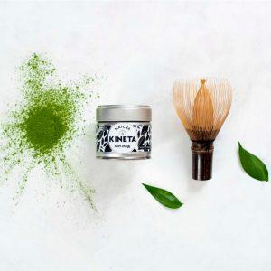 30g Tin Of Matcha Green Tea In Between A Chasen Matcha Whisk And Some Matcha Tea Powder