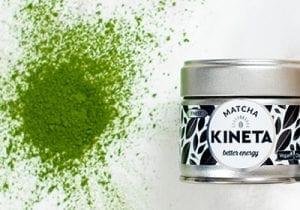30g Kineta Matcha Tea Tin Next To A Pile Of Matcha Green Tea Powder