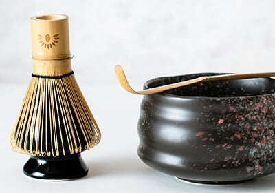 Chasen Matca Whisk On a Ceramic Holder Next To A Ceramic Chawan Matcha Bowl With A Chashuku Bamboo Spoon On Top