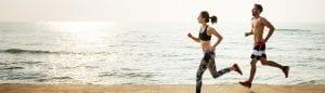Man And Woman Running Along A Beach