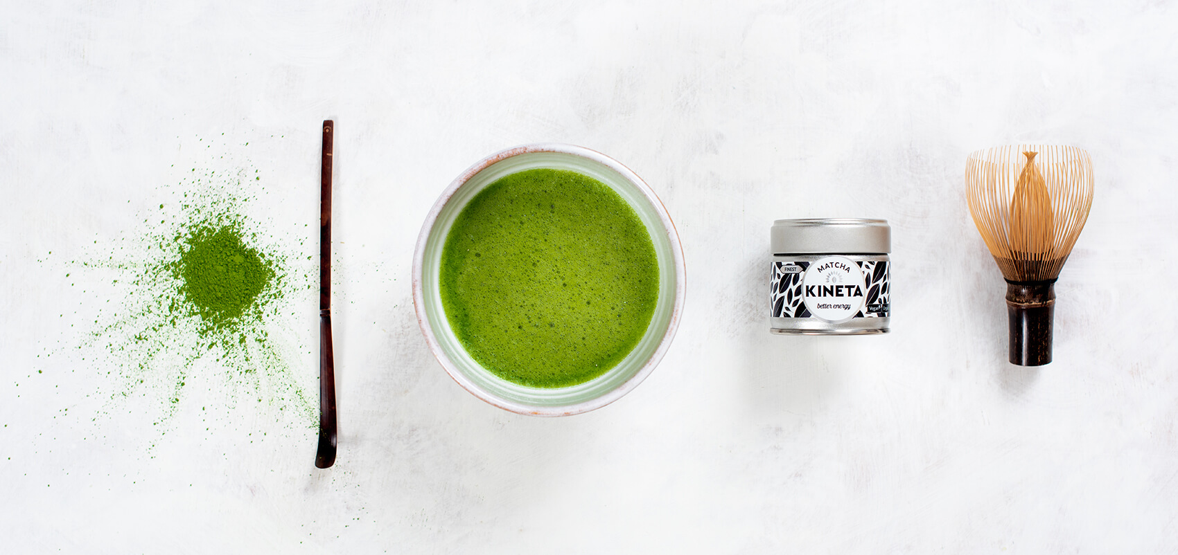 Kineta Finest Matcha Tea powder, bowl, whisk and bamboo spoon on a slate background