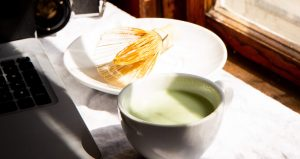 A Cup Of Japanese Matcha Tea And A Chasen Matcha Whisk On A Plate In Front Of A Laptop And Camera